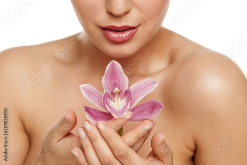 Foto Murales beautiful young woman hold an orchid on white background