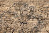 Old brick wall with graffiti fragments
