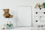 Teddy bear on white chair next to white poster with mockup in child's room interior. Real photo. Place for your graphic - 209029181