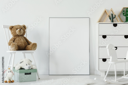 Foto Murales Teddy bear on white chair next to white poster with mockup in child's room interior. Real photo. Place for your graphic