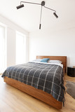 Lamp above wooden bed with patterned blanket in simple white bedroom interior. Real photo - 209029722