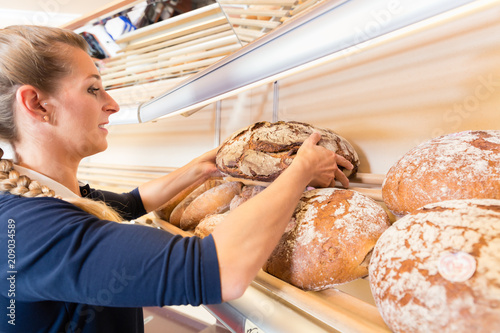 Leinwanddruck Bild Bakery woman putting bread in shop shelf to sell it