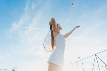 Woman serving the ball for a game of tennis on court © Kzenon