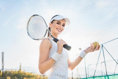 Kobieta gracz w tenisa pokazuje piłkę na sądzie