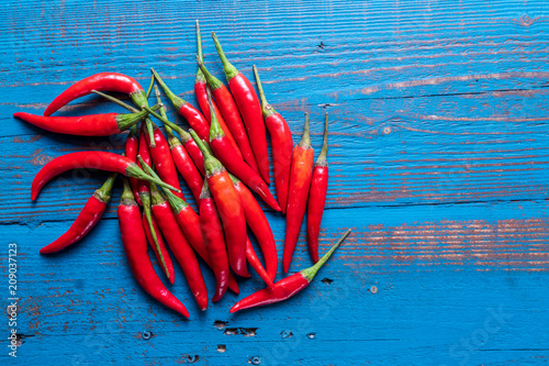 Aluminium Hot chili peppers Pile of chili hot peppers on blue wooden background.