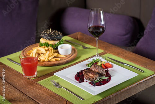 Grilled meat steak with raspberrie sauce on wooden background - 209037364
