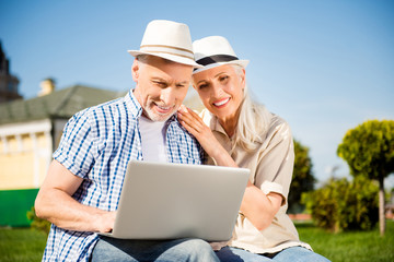 Portrait of lovely attractive spouses having video-call using laptop watching video searching website making online shopping chatting with friends. Apps electronic wireless device concept