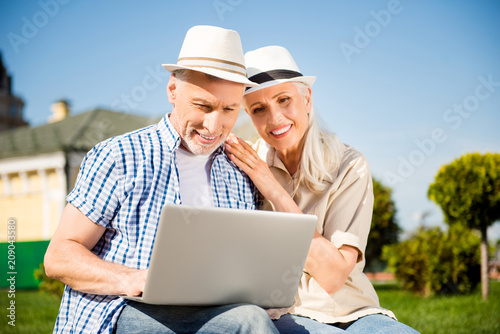 Leinwanddruck Bild Portrait of lovely attractive spouses having video-call using laptop watching video searching website making online shopping chatting with friends. Apps electronic wireless device concept