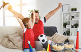 family of fans watching a football match on TV at home - 209043982