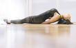Latin woman performs yoga posture in nice room.
