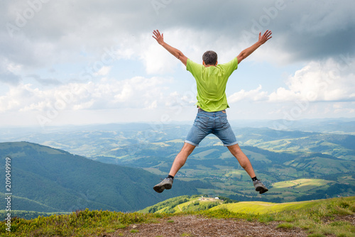 man jumping on the peak of the mountain