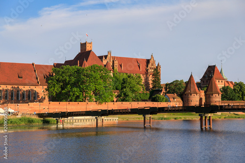 The wooden pedestrian bridge on the background of Teutonic Castle in Malbork, Poland © Castenoid