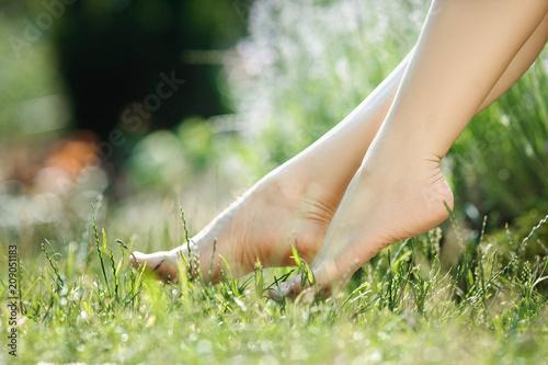 Leinwanddruck Bild female legs walking on green grass
