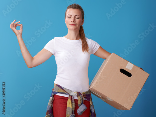 Fototapeta relaxed young woman with cardboard box doing yoga on blue