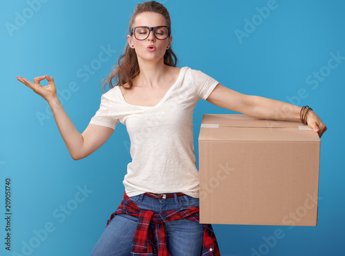 relaxed active woman with cardboard box doing yoga on blue