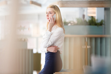 Charming young woman in formal suit talking on smartphone during lunch break in large spacious office in business center