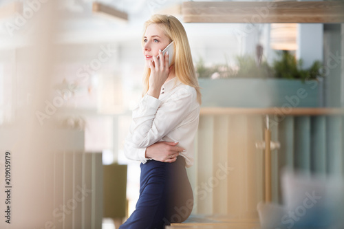 Charming young woman in formal suit talking on smartphone during lunch break in large spacious office in business center - 209059179