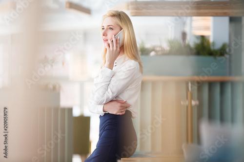 Powabna młoda kobieta opowiada na smartphone podczas przerwa na lunch w wielkim przestronnym biurze w centrum biznesu w formalnym kostiumu