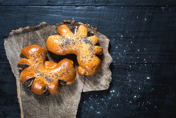 Sweet bun with poppy seed on wooden background. Top view. Copy space