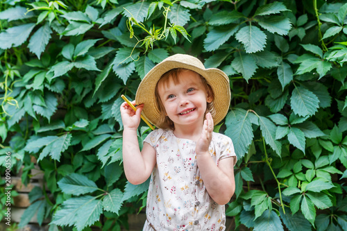 Foto Murales Little girl in straw hat with yellow pencil on background green plant leaves in garden summer.
