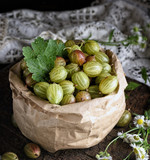 green gooseberries in a paper bag on a wooden board