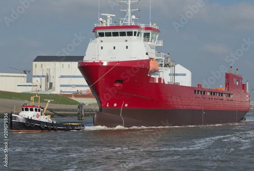 Fototapeta Towing boat with fcargo ship. Carier. Towing. Harbor Harlingen Netherlands