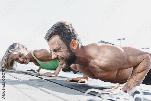 Leinwanddruck Bild Fit fitness woman and man doing fitness exercises outdoors at city