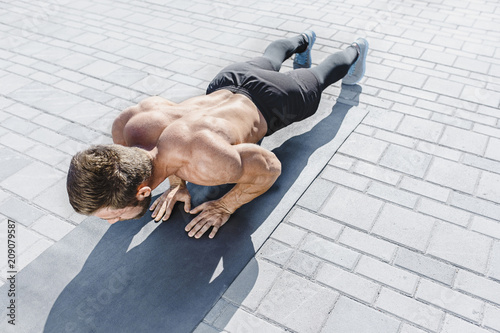 Fit fitness man doing fitness exercises outdoors at city © master1305