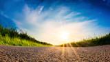 Rural road through green fields at sunrise - 209083152