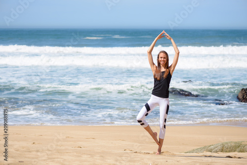 Smiling active young woman doing sports exercises on the beach