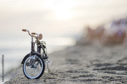 Aluminium Fiets bicycle toy on beach sunset time holiday