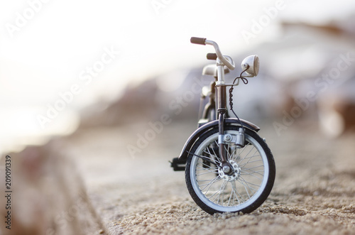 Fotobehang Fiets bicycle toy on beach sunset time holiday
