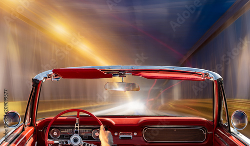 classic convertible driving at night through illuminated tunnel