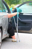 Disabled woman upgoing from a car. Transportation and travel for handicapped people. - 209104505