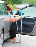 Disabled woman upgoing from a car. Transportation and travel for handicapped people. - 209104527