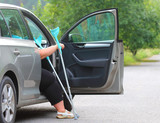 Disabled woman upgoing from a car. Transportation and travel for handicapped people. - 209104548