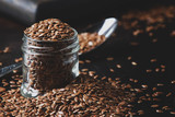 Flax or linen seeds in jar on brown stone background, selective focus - 209110999