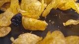 Fresh roasted potato chips falling on black surface and rolling towards camera. Slow motion and close up shot. - 209121702