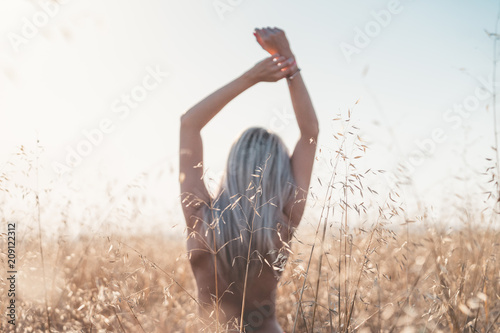 young woman enjoying freedom at wheat field