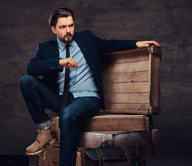 Portrait of a middle age businessman with stylish hair and beard dressed in jeans, jacket and tie, sitting on wooden boxes in a studio.