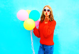 Cool girl sends an air kiss with colorful balloons on a blue background - 209127552