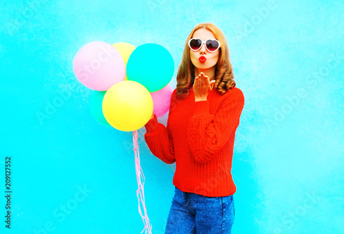 Cool girl sends an air kiss with colorful balloons on a blue background
