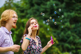 Couple blowing soap bubbles, having fun - 209128953