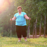 Overweight woman walking on forest trail. Slimming and active lifestyle theme.  - 209130139