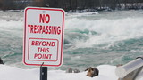 A plate with an inscription No trespassing. Dangerous for swimming and for living place. The stormy water of the river flows in the background. Niagara River in front of Niagara Falls