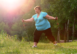 Overweight woman walking on forest trail. Slimming and active lifestyle theme.  - 209130182