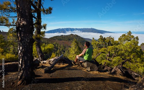 Leinwanddruck Bild Man sitting on the stone watching a volcanic landscape of pine forest with a Caldera de Taburiente on background, island of La Palma, Canary Islands, Spain