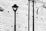 one elegant street electric lamppost on an indistinct background of an old brick wall of monochrome tone - 209134189