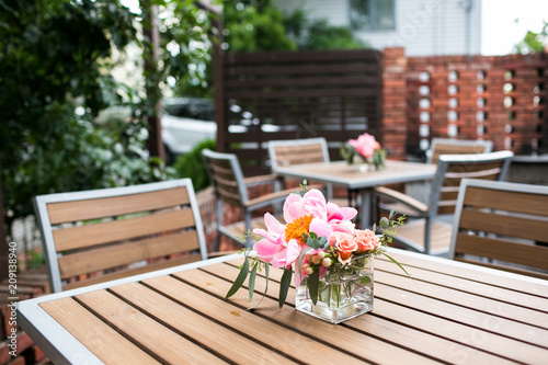 Wall mural Patio  with pink flowers sitting on outdoor tables