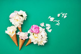 Ice cream cones with white peony flowers on green background. Summer concept. Copy space, top view